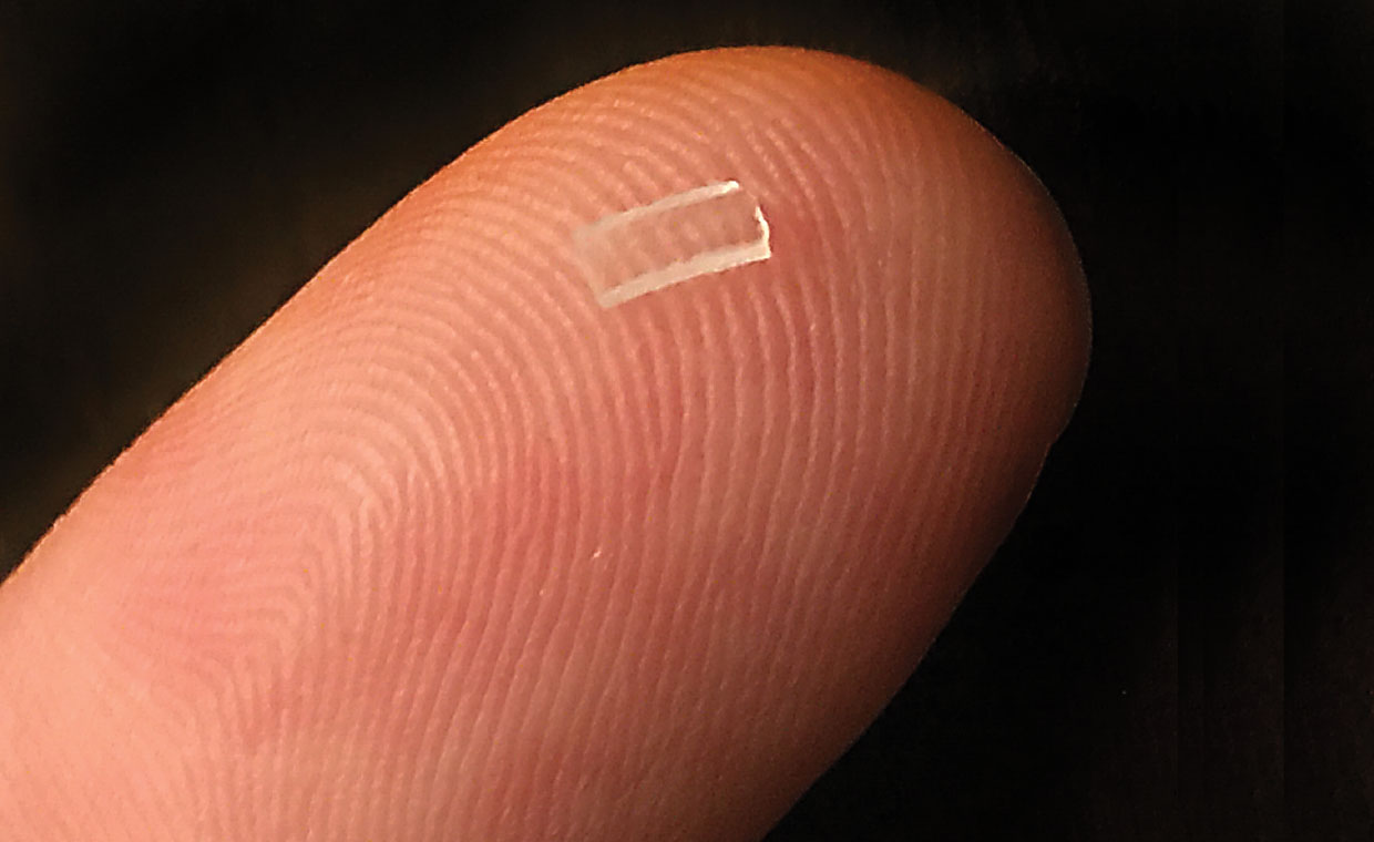 Close up of a finger with a clear square on it.