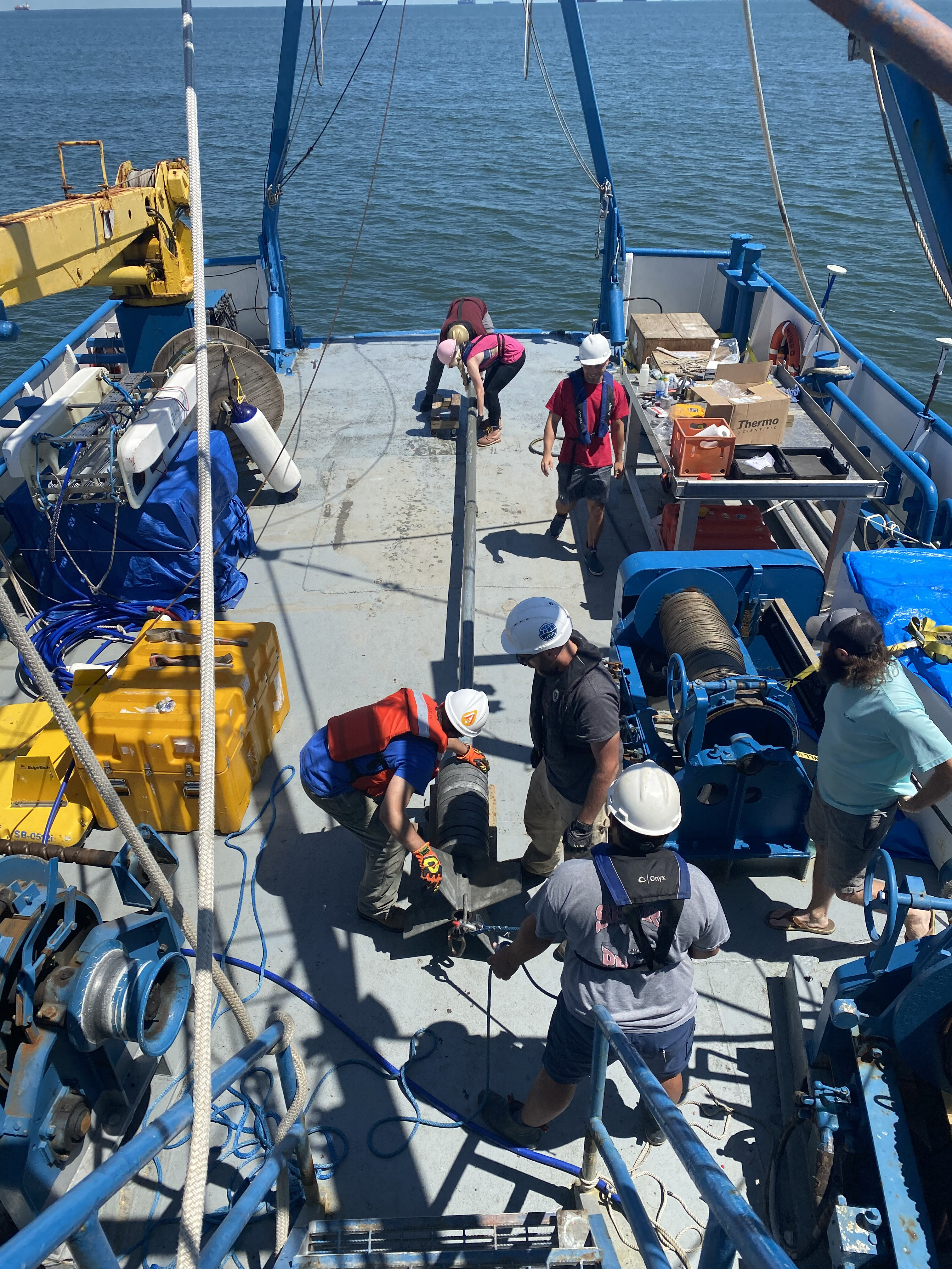 Researchers prepare to lower coring device into the water