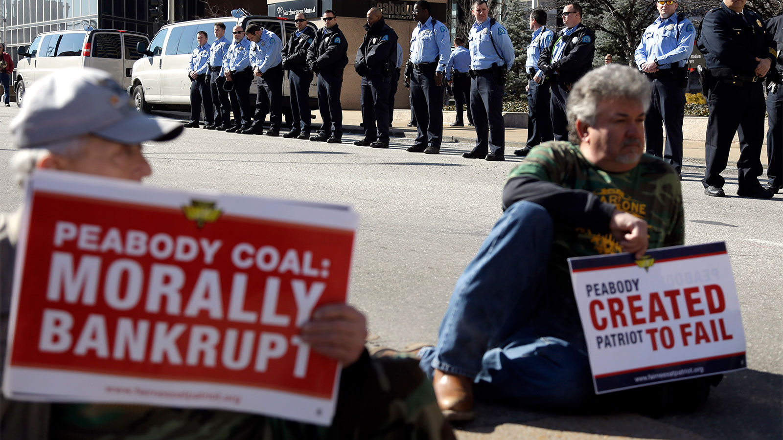 Two men holding signs protesting Peabody Energy with police in the background