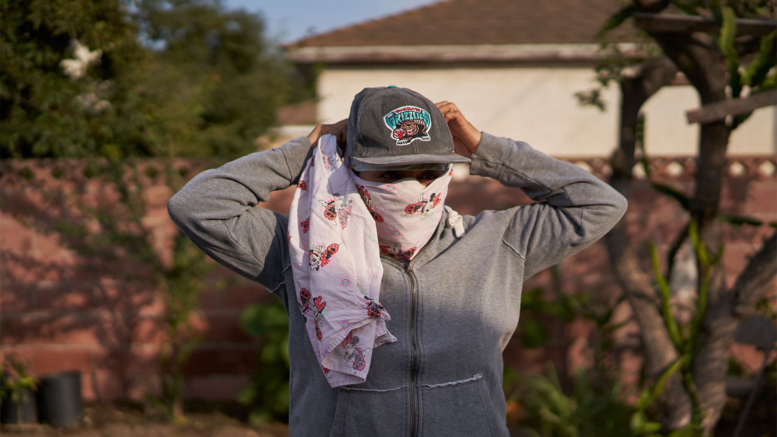 a woman ties a bandana around her face while wearing a hat and standing in front of a sunny house