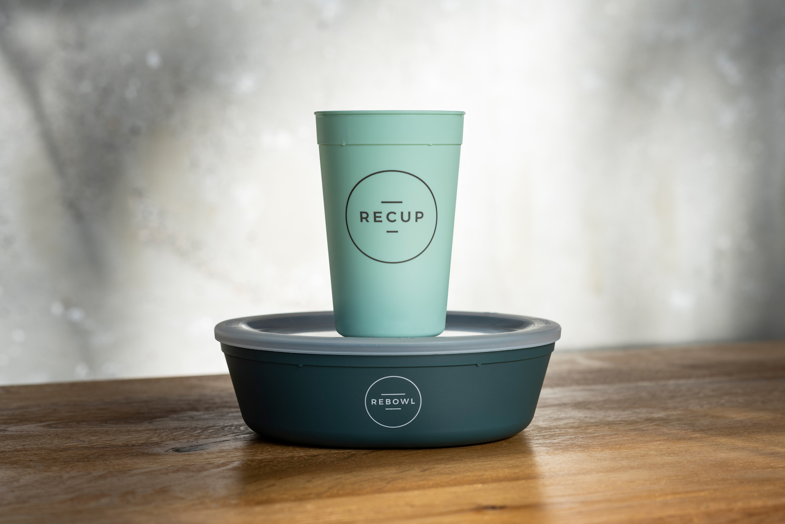 a green cup on top of a green bowl. Both are labeled ReCUP